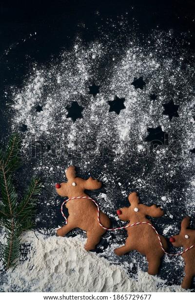 Vertical image of three reindeer gingerbread cookies