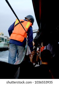 vertical image of ticket taker wear orange life jackets, he is working on the boat motion on canal with passengers, Bangkok, Thailand, 11 Jan 2018