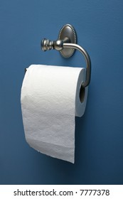 vertical image of toilet paper on roller on blue wall