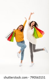 Vertical image of Two cheerful girls in sweaters with packages rejoices and looking at the camera over white background