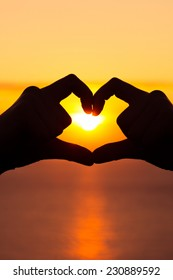 Vertical image of two hands forming a heart symbol at golden hour sunset