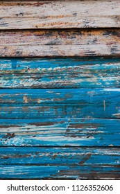 Vertical image of weathered wooden planks with chipped and scraped blue paint