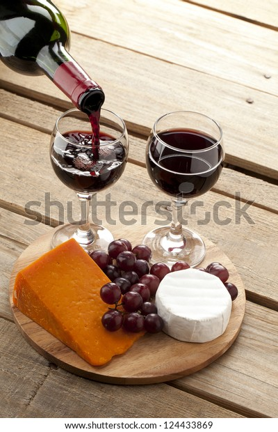 Vertical image of a wooden board with cheese and red grapes while someone pouring red wine in wine glass.