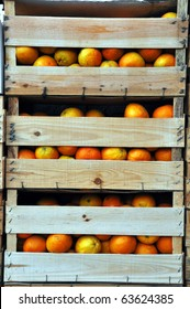 Vertical image of wooden crates with oranges.
