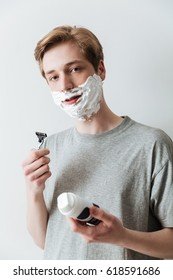 Vertical image of a young man in shaving foam which holding razor and looking at camera