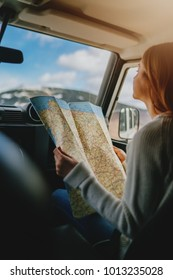 Vertical image of young traveler girl sitting in vintage car exploring map, beautiful woman with long hair traveling by car searching new direction, vintage lifestyle traveling, sunny weather