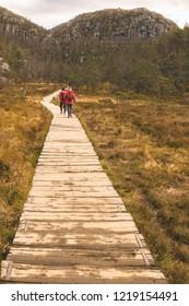 The vertical landscape of travelers treking on the wooden path, Preikestolen, Ryfylke, Norway.