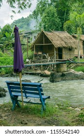Vertical landscape of vintage house beside the small river view and have woodbench and big umbrella foreground