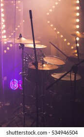 Vertical live music photo background, rock drum set  with cymbals and colorful blurred stage lights