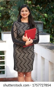 Vertical medium long portrait shot of modern Indian businesswoman wearing body-hugging dress standing on terrace holding red folder with papers