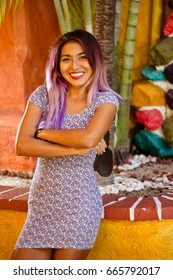 Vertical middle shot of young mexican woman standing with a colorful background and smiling to the camera.