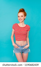 Vertical of nice cute adorable attractive lovely trendy cheerful positive red-haired girl with bun, wearing t-shirt and jeans shorts, hands in pockets, isolated on bright vivid blue background