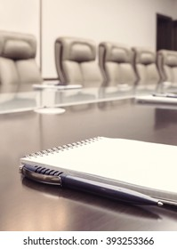 Vertical notepad for agenda kept on table in empty corporate conference room before business meeting