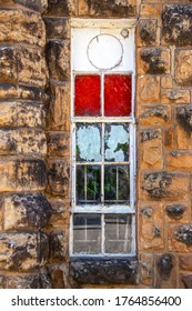 Vertical old grungy window in rustic rock building with peeling painted panes and a plastic inset with pipe used to stick out