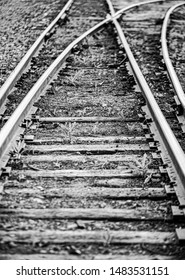 vertical orientation black and white image of train tracks moving in separate directions