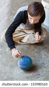 vertical orientation of boy with autism and down's syndrome sitting cross legged on a cement floor spinning a bright blue ball / Boy with Autism spins a Ball