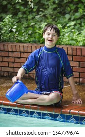 vertical orientation close up of a happy, smiling boy with autism and down's syndrome sitting cross legged at the edge of the pool with a bucket / Sensory Water Play