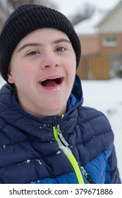 vertical orientation close up of a happy, smiling, teenage boy with autism and Down's syndrome outside playing in the snow / Teenager with Autism and Down's Syndrome playing outside on a snowy day