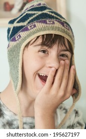 vertical orientation close up of a teenage boy with autism and down's syndrome, wearing a winter wool hat, with his hand on his face, looking surprised and happy / Surprised Teenage Boy
