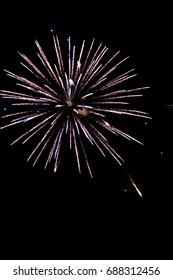 vertical orientation color image of fireworks exploding in the night sky on isolated black background with copy space / Fireworks exploding on isoloated black background