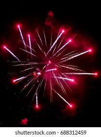 vertical orientation color image of fireworks exploding in a night sky on isolated black background, with copy space / Fireworks in hues of Red on isolated black background