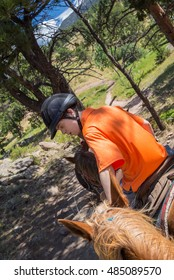 vertical orientation color image of a handsome teenage boy with autism and Down's syndrome in riding attire on horseback in the Rocky Mountains / Teen Boy with Autism and Down's Syndrome on horseback