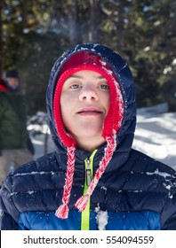 vertical orientation color image of a handsome teenage boy with autism and down's syndrome outside in a snow covered forest / Teenage Boy with Autism and Down's Syndrome Outside in Winter