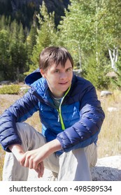 vertical orientation color image of a happy, smiling, teenage boy with autism and down's syndrome outside, taking a break from hiking / Outdoor Recreation for Special Needs Children