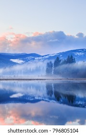 Vertical orientation color image of McArthur Lake in northern Idaho at sunset on a cloudy evening
