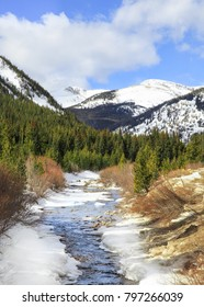 Vertical orientation color image of Rollins Pass, Colorado, USA with a partly frozen stream in the foreground and snow covered mountains in the background