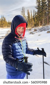 vertical orientation color image of a smiling, happy teenage boy with autism and Down's Syndrome outside snowshoeing with a forest background/ Boy with Autism and Down's Syndrome learning to Snowshoe