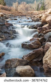 vertical orientation color image, taken with a very slow shutter speed to show the movement of water in a creek through a rocky landscape / Rocky Mountain waterfall and scenery