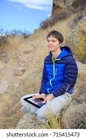 vertical orientation color image of a teenage boy with autism and Down's Syndrome with his tablet device outside / Teenager with Autism and Down's Syndrome outside with his Tablet Device