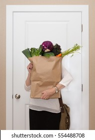 vertical orientation color image of a woman in business attire holding a paper bag overflowing with veggies / Adding Fresh Vegetables to your Diet