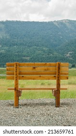 vertical orientation of a single, empty, wooden bench in the foreground, with the majestic Selkirk Mountain Range in the background, with copy space / Spectacular Northern Idaho - Vertical
