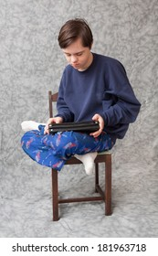 vertical orientation of a teenage boy with autism and down's syndrome sitting on a chair while he plays with a tablet device / Apps that Appeal to kids with Autism