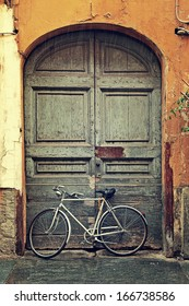 Vertical oriented image of bicycle leaning against old wooden door at the entrance to house on rainy day in Alba, Italy.