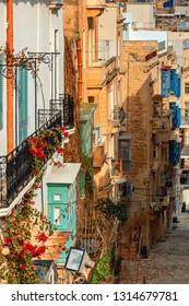 Vertical oriented image of typical stone buildings with colorful balconies along narrow street in Valletta, Malta.