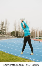 Vertical outdoors shot of a woman doing the warm up before training.