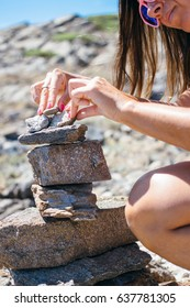 Vertical outdoors shot of woman sitting and putting stones in a roll.