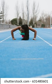Vertical outdoors shot of a young black woman doing push-ups on a stadium.