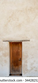 Vertical panorama perspective of an old mission wooden door against a white washed plaster wall / Wooden Door against White Washed Plaster Wall  / An Old Mission Door