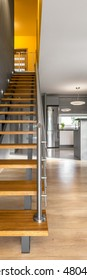 Vertical panorama of simple and modern wooden stairs with chromed railing