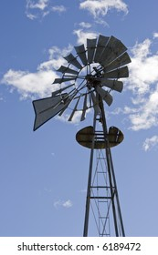 Vertical photo of antique style windmill against a blue sky with white clouds.