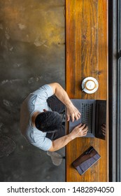 Vertical photo of Asian freelancer using laptop at rustic coffeeshop