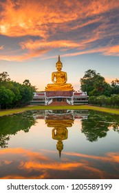 Vertical photo Beautiful Big Golden Buddha statue sunset sky in Thailand temple,khueang nai District, Ubon Ratchathani province, Thailand.Amazing Buddha image with sunny sky clouds.
