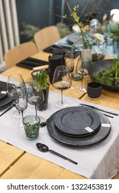 Vertical photo of beautiful holiday table setting for family dinner. Empty glasses, plates and other items standing near green plant decorations