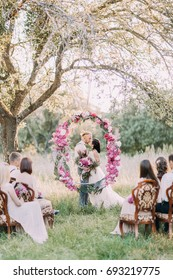 The vertical photo of the beautiful wedding ceremony in the sunny forest. The kissing newlyweds are standing behind the wedding peonies arch while guests are sitting on the chairs.