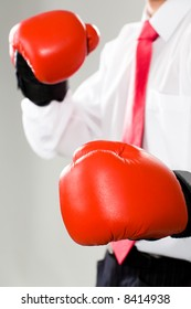 Vertical photo of a business man in red boxing gloves