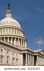 vertical photo of The Capitol, Washington DC, american flag waving, blue sky